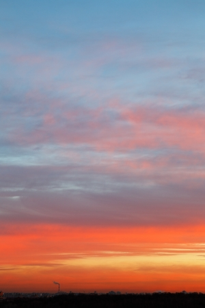 early sunrise sky with blue and pink clouds over dark city photo