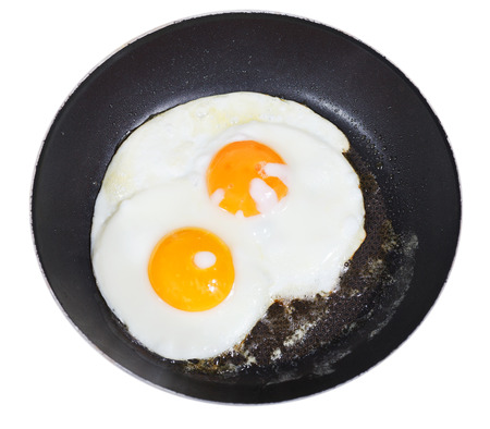 top view of two fried eggs in frying pan isolated on white background photo
