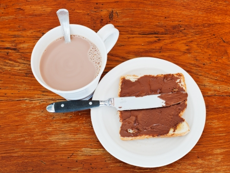 sweet sandwich from fresh toast with chocolate spread, table knife and cup of hot chocolate on wooden table photo