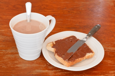cup of hot chocolate and sweet sandwich from fresh toast with chocolate spread, table knife on wooden table photo