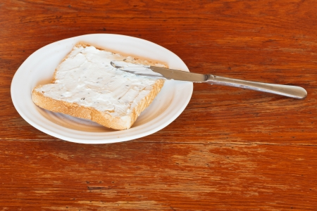 sandwich from toast and soft cheese with herbs on white plate, table knife on wooden table photo