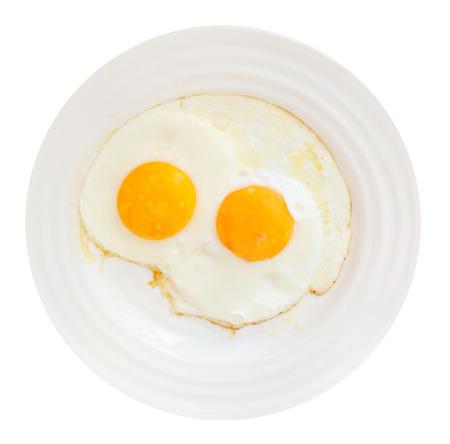 bovenaanzicht van een witte plaat met twee gebakken eieren op een witte achtergrond