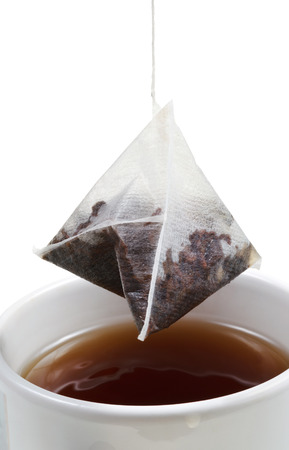 brewing of tea in mug with tea bag close up isolated on white background photo