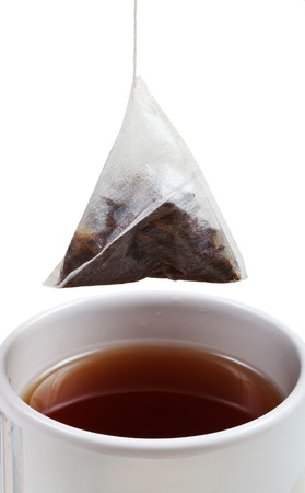brewing of tea in cup with tea bag close up isolated on white background photo