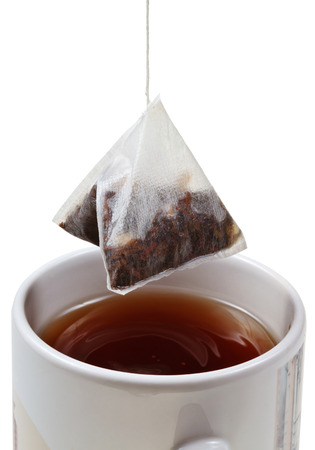 tea bag over brewing tea in mug close up  photo