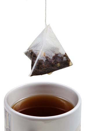 tea bag over brewing tea in cup close up isolated on white background photo