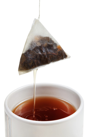 removing of tea bag from cup with brewing tea close up isolated on white background photo