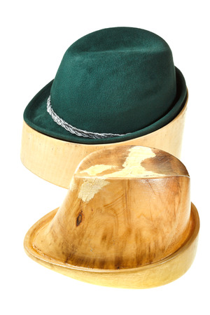 hunting felt hat on linden wooden hat block and additional hat block isolated on white background photo