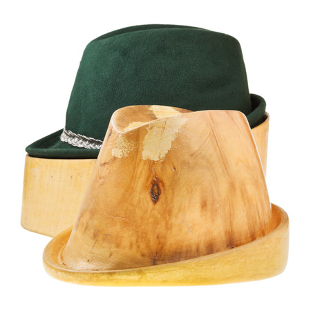 linden wooden hat block and green tyrolean felt hat isolated on white background photo