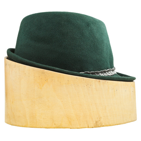 side view of green tyrolean felt hat on linden wood hat block isolated on white background photo