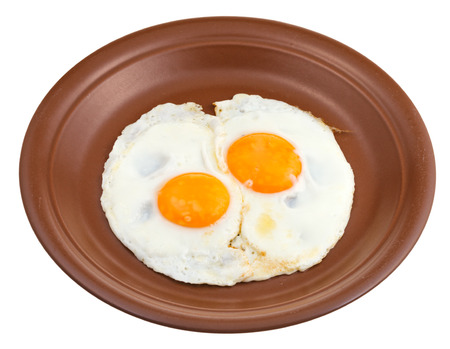 two fried eggs on ceramic brown plate isolated on white background photo