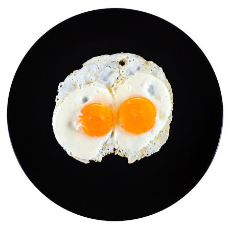 top view of two fry eggs on ceramic black plate isolated on white background photo
