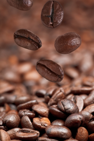 focus on foreground: few falling beans and dark roasted coffee beans background with focus foreground Stock Photo