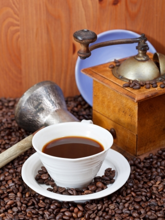 cup of coffee and roasted coffee beans with retro manual mill, coffee pot