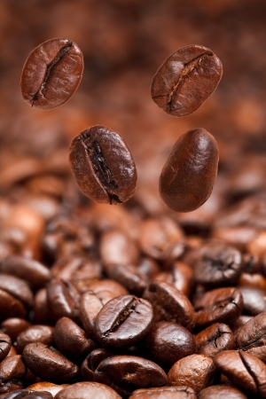 focus on foreground: four falling beans and dark roasted coffee beans background with focus foreground