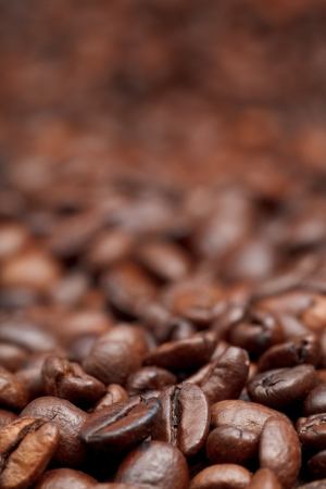 focus on foreground: strong roasted coffee beans background with focus foreground