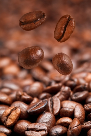 four falling coffee beans and roasted coffee background with focus foreground photo