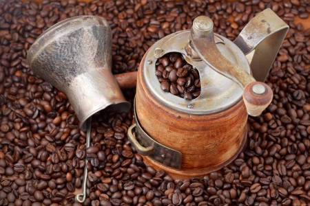 top view of retro manual coffee mill and copper pot on many roasted coffee beans photo