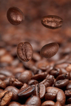focus on foreground: four falling beans and roasted coffee beans background with focus foreground