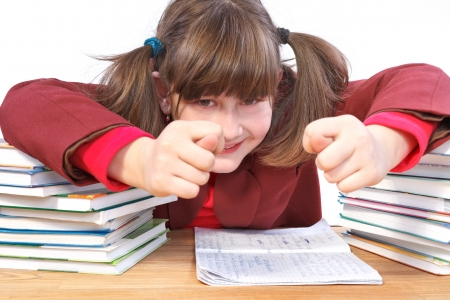 schoolwork: smiling schoolgirl unwilling to do schoolwork and shows fig