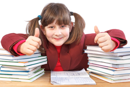 glad schoolgirl did schoolwork and shows thumb-up photo
