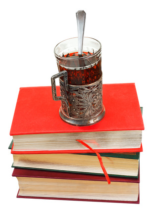 retro glass of tea on stack of books isolated on white background photo