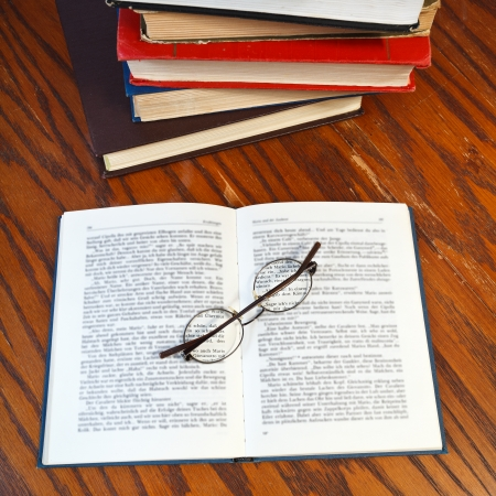 above view of blank open book and eyeglasses on wooden table photo