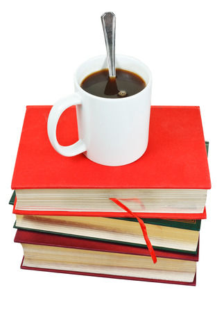 mug of coffee on stack of books isolated on white background photo
