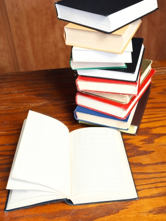 top view of blank open book on wooden table near bookcases photo