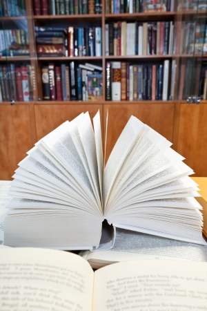 fanned: fanned open books with blur font on wooden table near bookcases