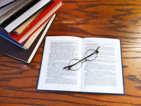 above view of blank open book and glasses on wooden table photo