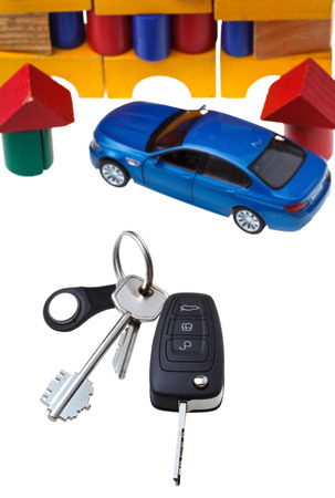 above view of door keys, vehicle key, new blue car model close up and wooden block toy house isolated on white background photo