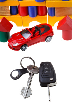 door keys, vehicle key, new red car model close up and wooden block toy house isolated on white background photo