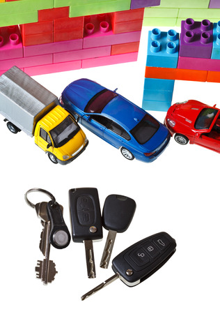 top view of door key, vehicle keys, three model cars and plastic block house isolated on white background photo