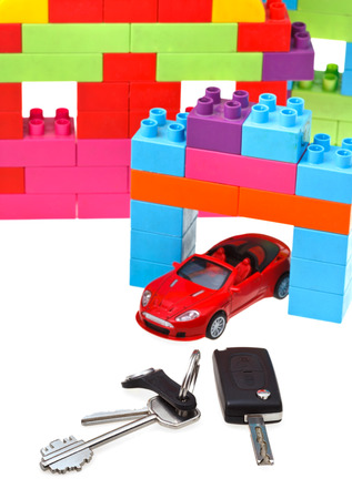 door key, vehicle keys close up, red model car and plastic block house isolated on white background photo