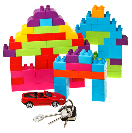 plastic block house, door and car keys, red model car isolated on white background photo