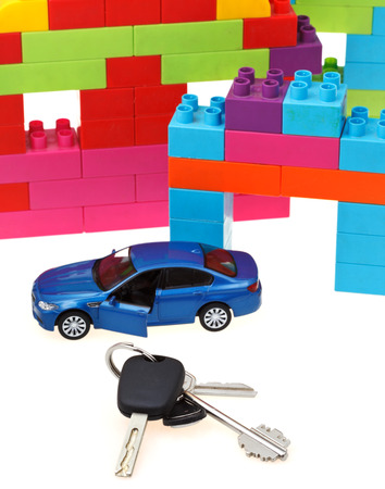 door key, vehicle keys close up, blue model car and plastic block house on white background photo