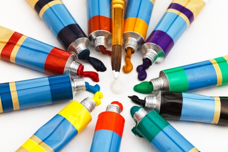spot the difference: round paintbrush and set of multicolored tubes with squeezed watercolors
