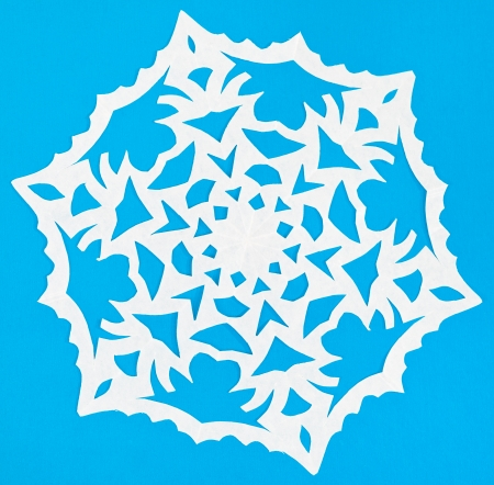 hand made cut out white snowflake on blue paper photo