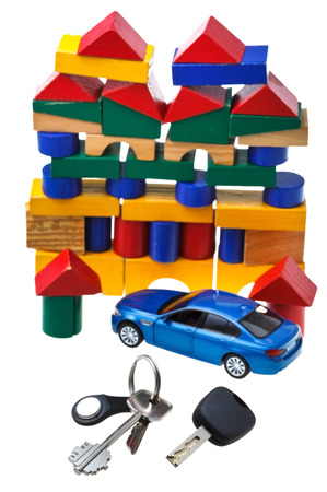 above view of door keys, vehicle key, new blue car model and wooden block toy house isolated on white background photo