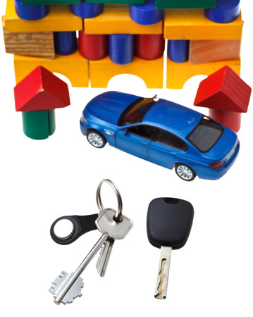 door keys, vehicle key, new blue car model close up and wooden block toy house isolated on white background photo