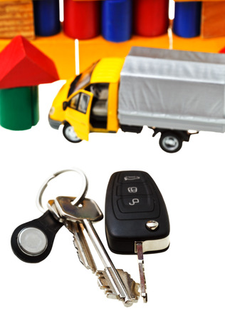 above view of door keys, vehicle key, new truck model and wooden block toy house isolated on white background photo