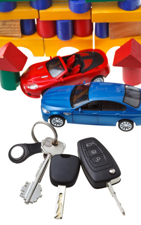 above view of door keys, vehicle keys, two car models and wooden block toy house isolated on white background photo