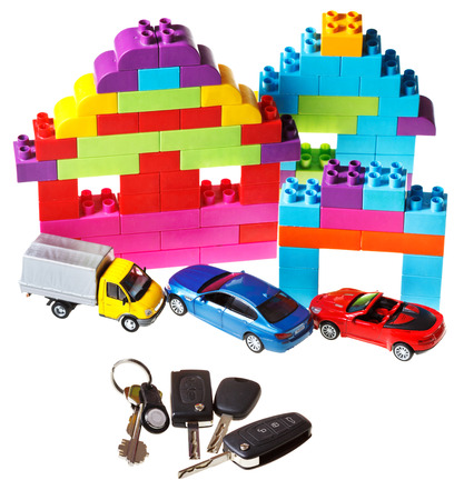 door key, vehicle keys, three model cars and plastic block house isolated on white background photo