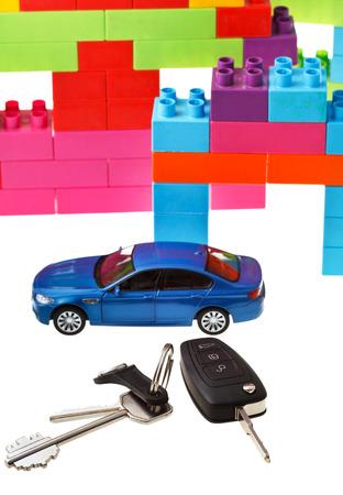 door key, vehicle keys close up, blue model car and plastic block house isolated on white background photo