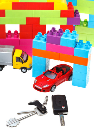 door key, vehicle keys, truck and car models and plastic block house isolated on white background photo
