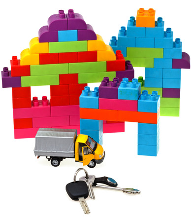 plastic block house, door and car keys, model truck on white background photo