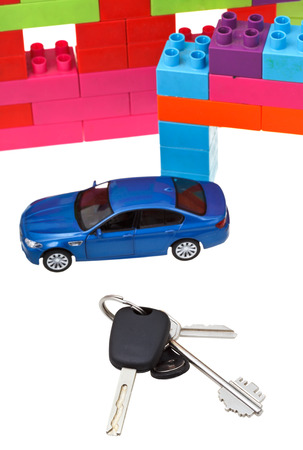 door and car keys close up, blue model car and plastic block house isolated on white background photo