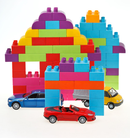 plastic block house and three model cars on white background photo