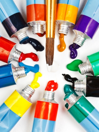round paintbrush and circle from multicolored tubes with squeezed watercolors photo